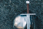 Knight's helmet and shiny metal lying on the ground, it put an old steel sword with leather handle.