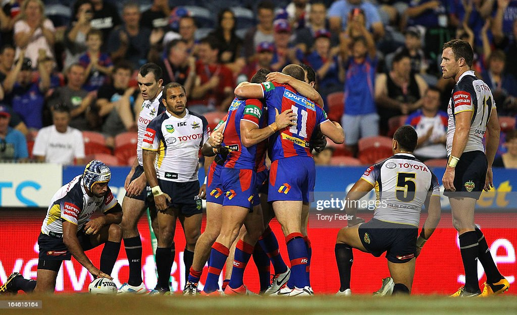 Knights players celebrate a try while Cowboys players look dejected during the round three NRL match between the Newcastle Knights and the North Queensland Cowboys at Hunter Stadium on March 25, 2013 in Newcastle, Australia.