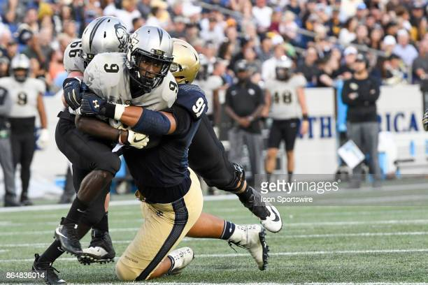 Knights running back Adrian Killins Jr runs and is brought down by Navy Midshipmen defensive end Tyler Sayles on October 21 at Navy Marine Corps...