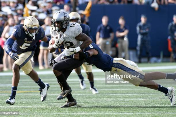 Knights running back Taj McGowan runs for a first down in the first half against Navy Midshipmen safety Sean Williams on October 21 at Navy Marine...