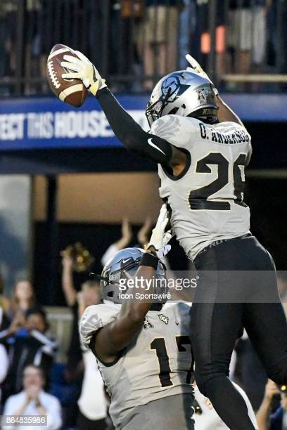 Knights wide receiver Otis Anderson is lifted up by wide receiver Marlon Williams after scoring on a fourth quarter run against the Navy Midshipmen...