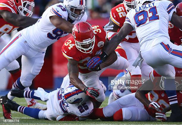 Knile Davis of the Kansas City Chiefs is tackled by Da'Norris Searcy of the Buffalo Bills as he returns a punt during NFL game action at Ralph Wilson...