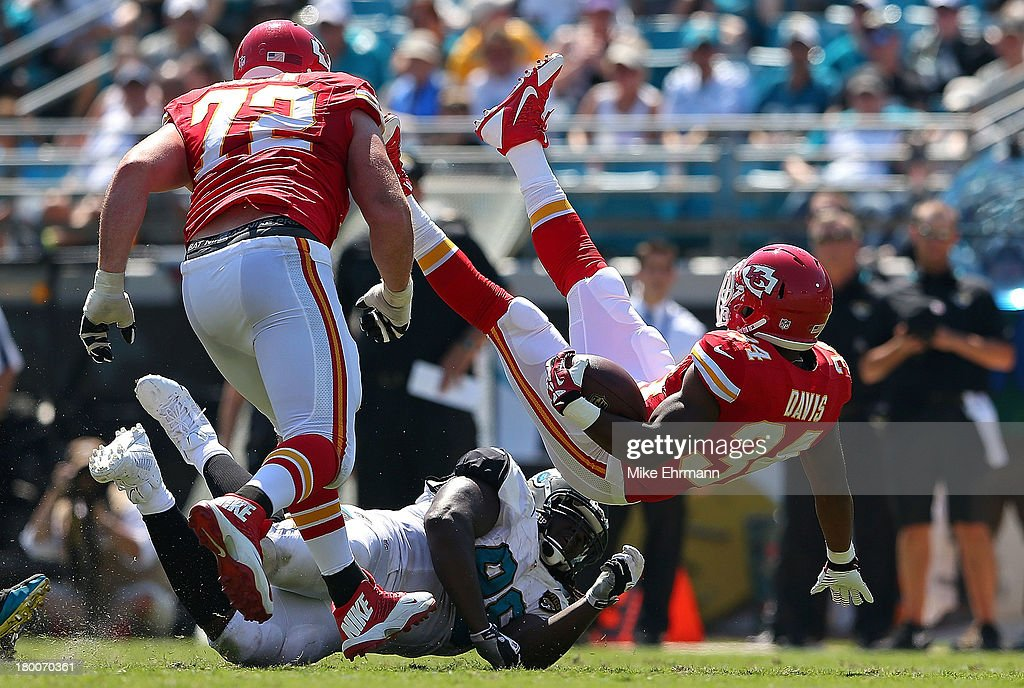 Knile Davis #34 of the Kansas City Chiefs is tackled by Sen'Derrick Marks #99 of the Jacksonville Jaguars during a game at EverBank Field on September 8, 2013 in Jacksonville, Florida.