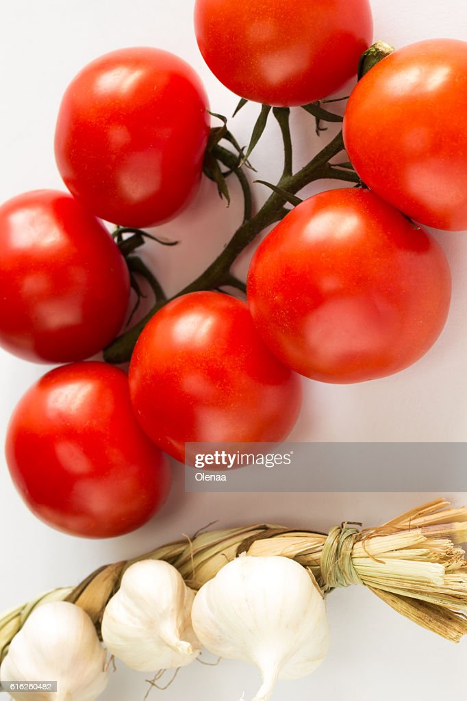 Knitted garlic and twig red tomatoes  on white : Stock Photo