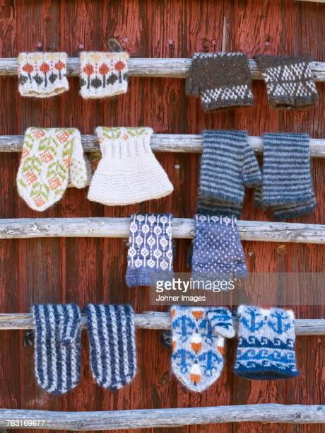 Knitted gloves hanging against wooden wall