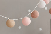 Knitted lights garland for party - christmas or valentines day, wedding decorations. Close-up shot isolated on gray wall background.