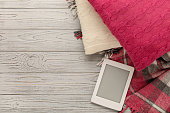 Knitted pillows, plaid and eBook on a light wooden background. Top view. Flat lay.