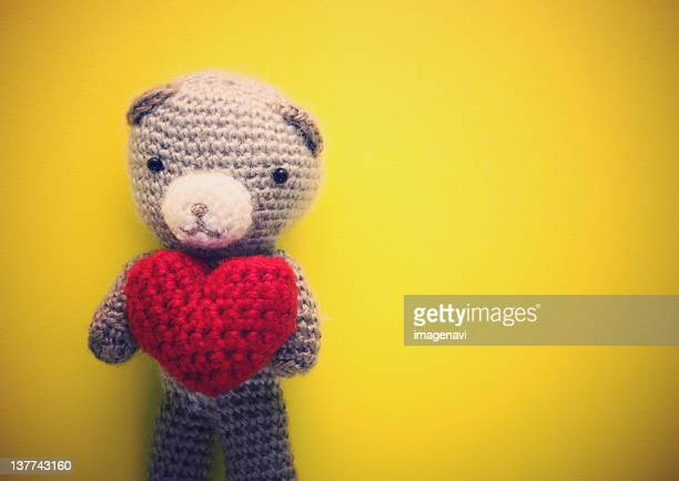 Knitted teddy bear holding heart