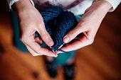 The woman knits woolen clothes. Knitting needles. Close-up. Natural wool.