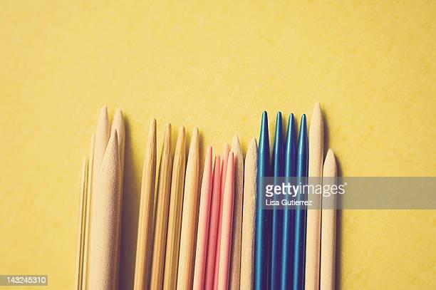 Knitting needles on yellow background
