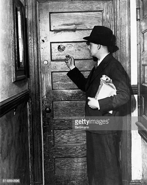 Knocking at door of a speakeasy during Prohibition A man with a package approaches a door with a protective peep hole Photograph 1930's BPA