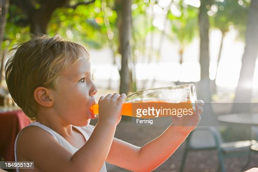 Knocking it back at the beach bar, a child drinking.