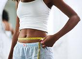 Closeup shot of an unrecognizable woman measuring her waist