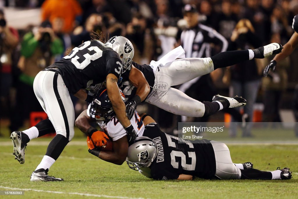 <a gi-track='captionPersonalityLinkClicked' href=/galleries/search?phrase=Knowshon+Moreno&family=editorial&specificpeople=3986554 ng-click='$event.stopPropagation()'>Knowshon Moreno</a> #27 of the Denver Broncos gets tackled by <a gi-track='captionPersonalityLinkClicked' href=/galleries/search?phrase=Tyvon+Branch&family=editorial&specificpeople=4517063 ng-click='$event.stopPropagation()'>Tyvon Branch</a> #33, <a gi-track='captionPersonalityLinkClicked' href=/galleries/search?phrase=Matt+Giordano&family=editorial&specificpeople=1826206 ng-click='$event.stopPropagation()'>Matt Giordano</a> #27 and <a gi-track='captionPersonalityLinkClicked' href=/galleries/search?phrase=Philip+Wheeler&family=editorial&specificpeople=2253975 ng-click='$event.stopPropagation()'>Philip Wheeler</a> #52 of the Oakland Raiders at Oakland-Alameda County Coliseum on December 6, 2012 in Oakland, California.