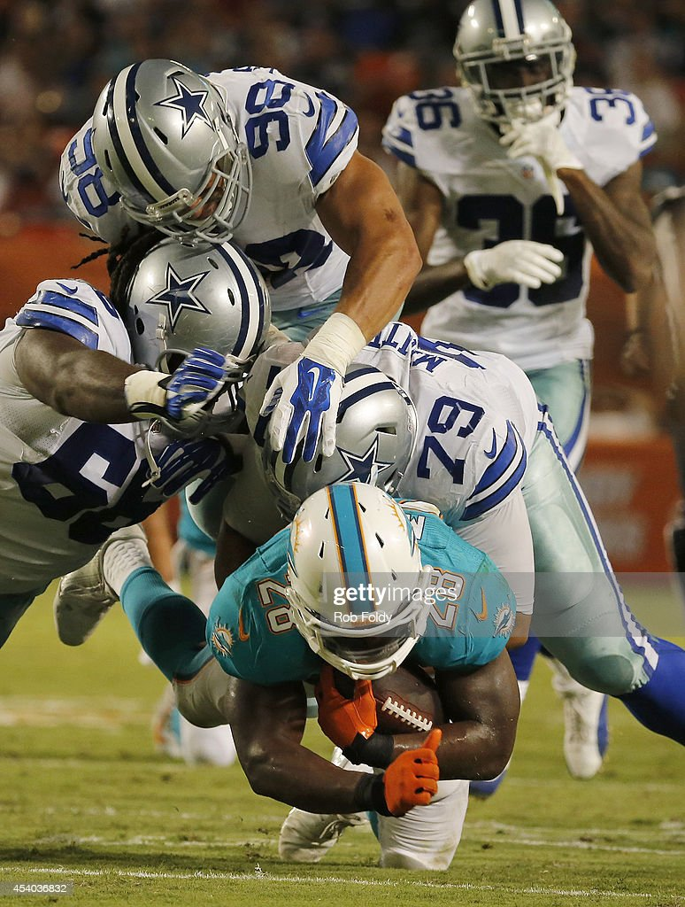 Knowshon Moreno #28 of the Miami Dolphins is brought down by a host of Dallas Cowboys defenders including Stephen Goodin #79 in the second quarter during a preseason game at Sun Life Stadium on August 23, 2014 in Miami Gardens, Florida.