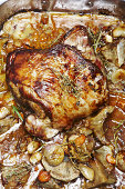 Knuckle of lamb with thyme and vegetables in roasting tin