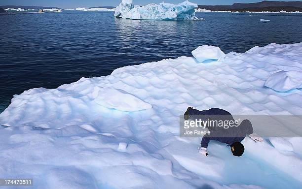 Knud Sakaessen drinks the melted ice gathered on an iceberg that broke off from the Jakobshavn Glacier as he takes some of the ice on July 21 2013 in...