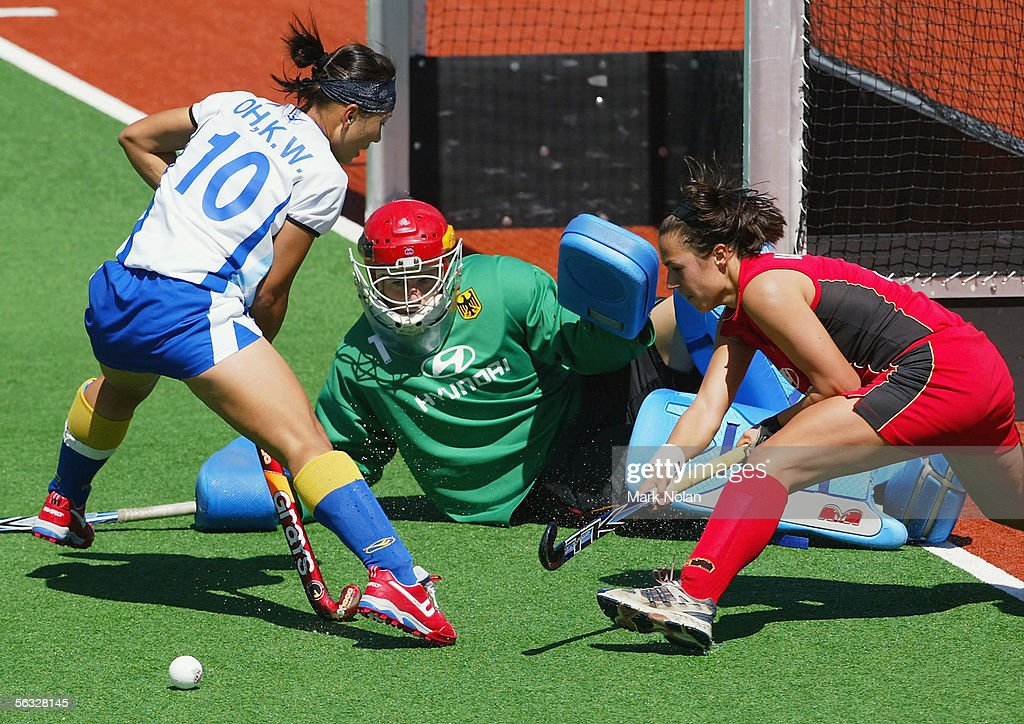 Ko Woon Oh of South Korea attacks as goal keeper Yvonne Frank and defender Tina Bachmann of Germany defend their goal during the Women's Hockey...