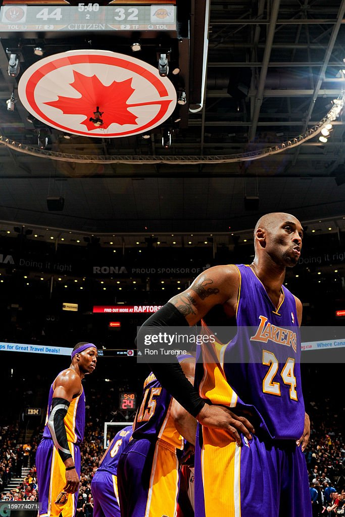 Kobe Bryant #24 and Dwight Howard #12 of the Los Angeles Lakers wait to resume action against the Toronto Raptors on January 20, 2013 at the Air Canada Centre in Toronto, Ontario, Canada.