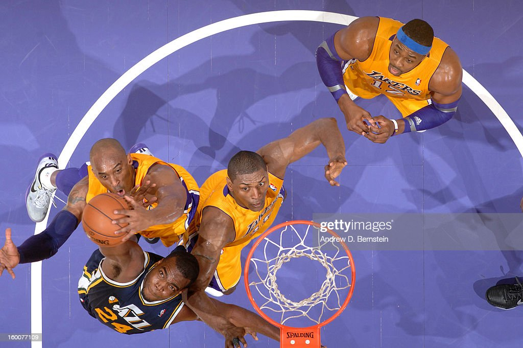 Kobe Bryant #24 and Metta World Peace #15 of the Los Angeles Lakers reach for a rebound against Paul Millsap #24 of the Utah Jazz at Staples Center on January 25, 2013 in Los Angeles, California.