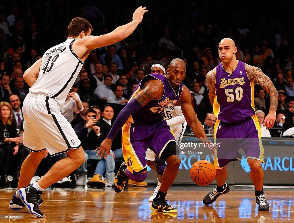 Kobe Bryant #24 and Robert Sacre #50 of the Los Angeles Lakers in action against Kris Humphries #43 of the Brooklyn Nets at Barclays Center on February 5, 2013 in the Brooklyn borough of New York City.The Lakers defeated the Nets 92-83.