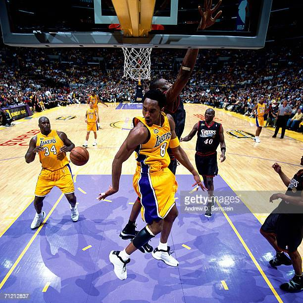 Kobe Bryant dishes to teammate Shaquille O'Neal of the Los Angeles Lakers while being defended by Dikembe Mutombo of the Philadelphia 76ers during...