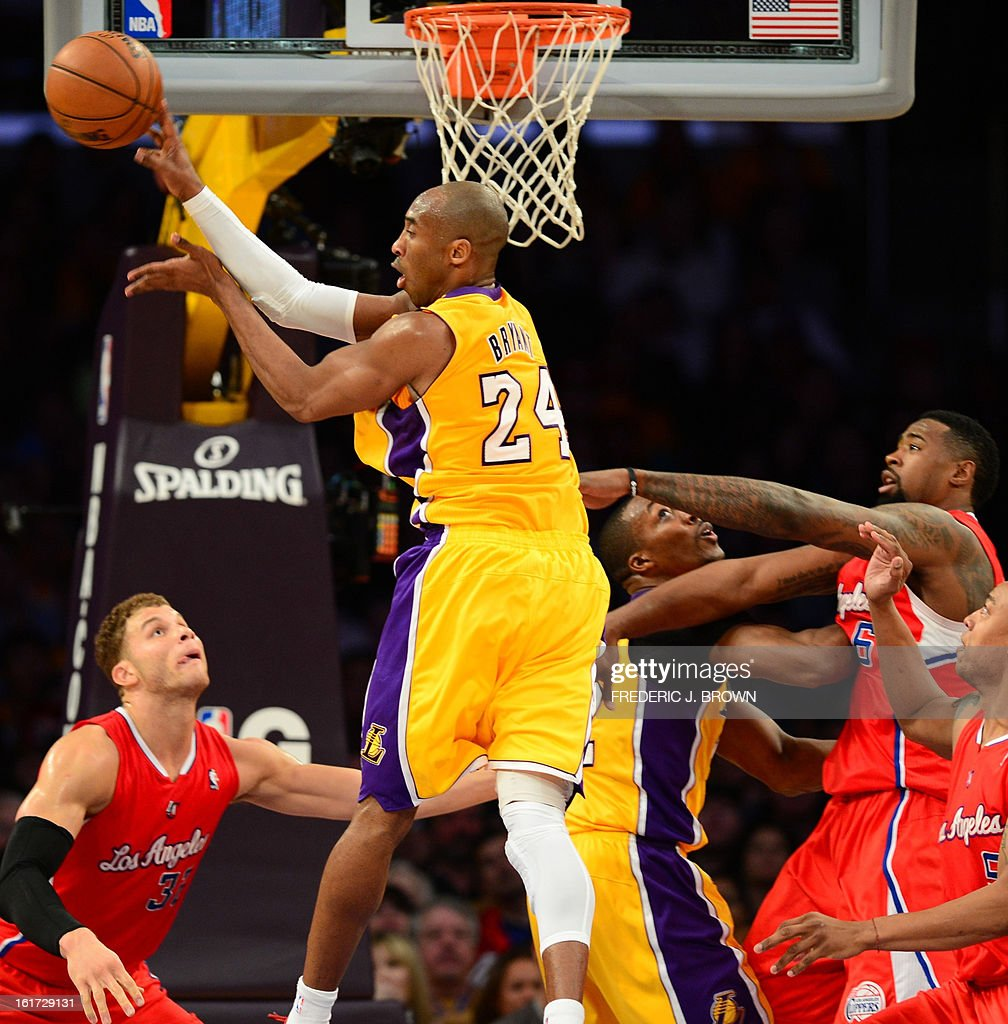 Kobe Bryant (C) of the LA Lakers passes off under the basket against the LA Clippers during their NBA game on February 14, 2013 at Staples Center in Los Angeles, California. AFP PHOTO / Frederic J. BROWN