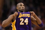 Kobe Bryant of the Los Angeles Lakers adjusts his jersey during the NBA game against the Phoenix Suns at US Airways Center on February 19 2012 in...