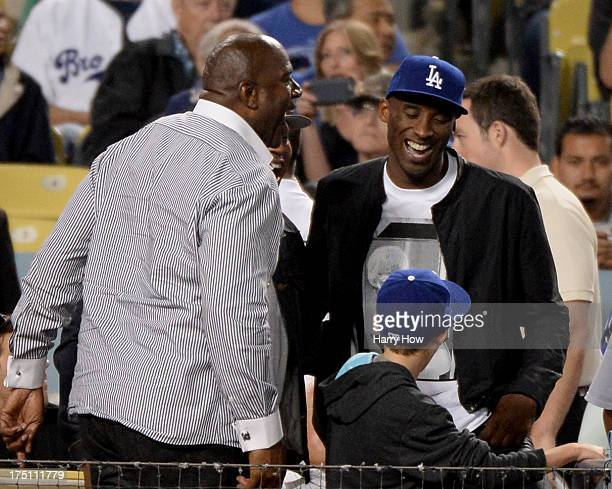 Kobe Bryant of the Los Angeles Lakers and Magic Johnson laugh during the game against the New York Yankees at Dodger Stadium on July 31 2013 in Los...