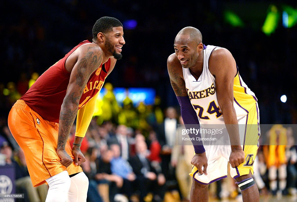 Kobe Bryant #24 of the Los Angeles Lakers and Paul George #13 of the Indiana Pacers smile after Bryant hit a three-point basket with time running out in the fourth quarter of the basketball game at Staples Center November 29, 2015, in Los Angeles, California.