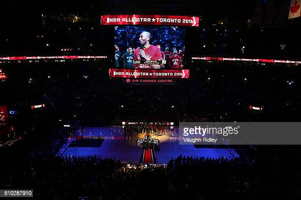 Kobe Bryant of the Los Angeles Lakers and the Western Conference speaks as his teammates and the Eastern Conference team look on with Magic Johnson...