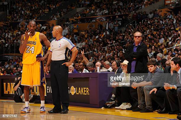 Kobe Bryant of the Los Angeles Lakers argues a call while actor Jack Nicholson looks on in the fourth quarter against the Denver Nuggets in Game Two...
