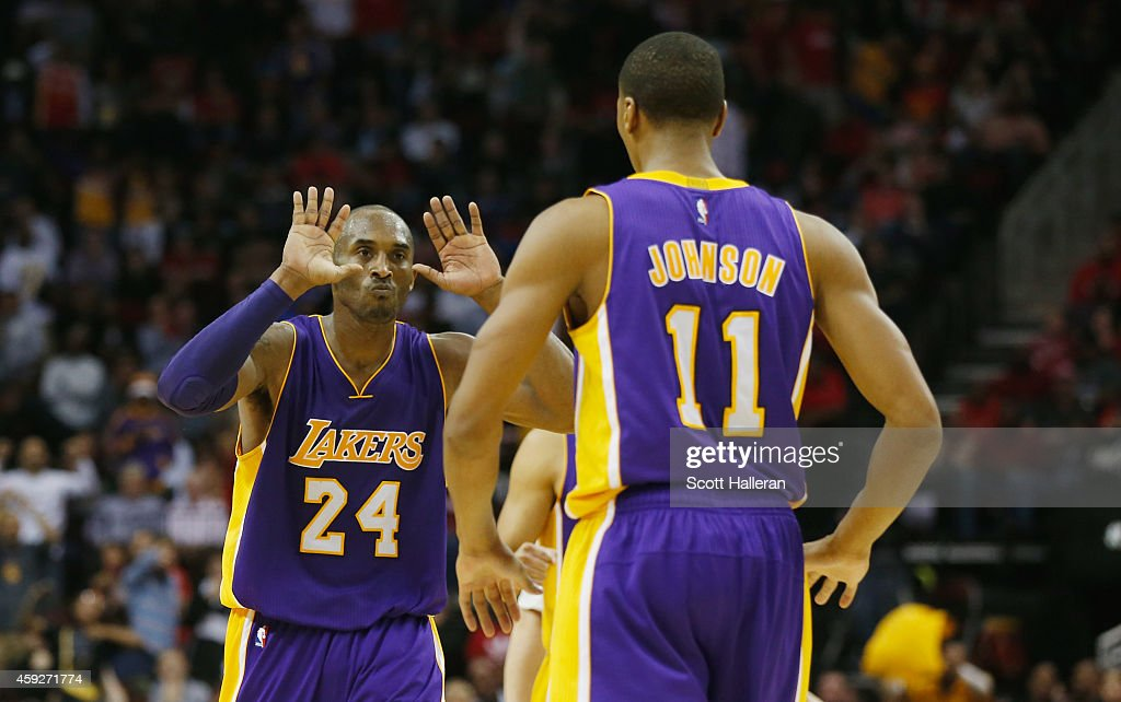 Kobe Bryant #24 of the Los Angeles Lakers celebrates a play with Wesley Johnson #11during their game against the Houston Rockets at the Toyota Center on November 19, 2014 in Houston, Texas.