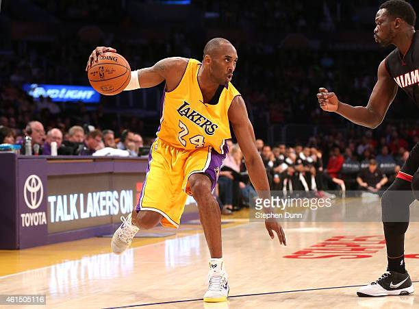 Kobe Bryant of the Los Angeles Lakers controls the ball against Luol Deng of the Miami Heat at Staples Center on January 13 2015 in Los Angeles...