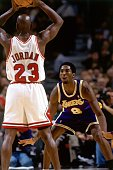 Kobe Bryant of the Los Angeles Lakers digs in on defense against Michael Jordan of the Chicago Bulls during a 1998 NBA game at the United Center in...