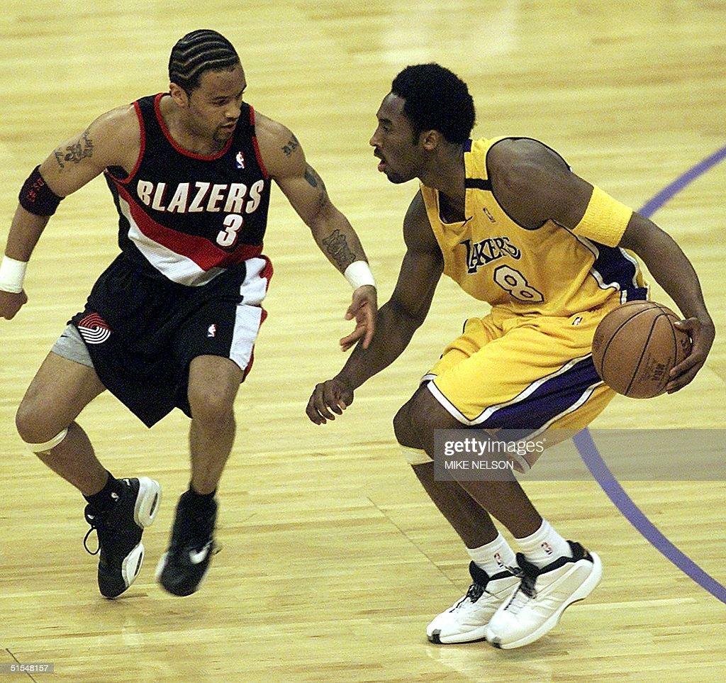 Kobe Bryant R of the Los Angeles Lakers dribbles