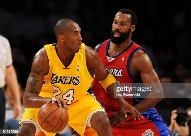 Kobe Bryant of the Los Angeles Lakers drives against Baron Davis of the Los Angeles Clippers during a preseason game at Staples Center on October 18...
