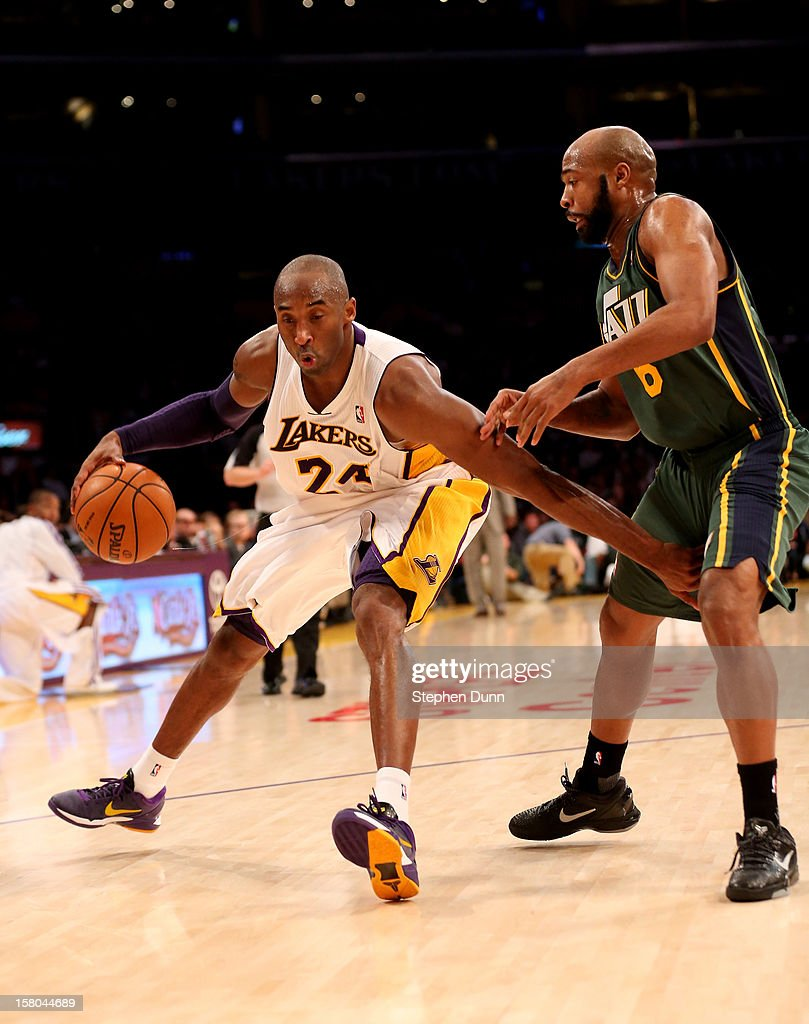 Kobe Bryant #24 of the Los Angeles Lakers drives against Jamaal Tinsley #6 of the Utah Jazz at Staples Center on December 9, 2012 in Los Angeles, California. The Jazz won 117-110.