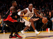 Kobe Bryant of the Los Angeles Lakers drives against Terrence Ross of the Toronto Raptors at Staples Center on November 30 2014 in Los Angeles...