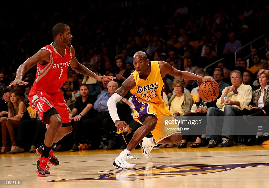 Kobe Bryant of the Los Angeles Lakers drives against Trevor Ariza of the Houston Rockets at Staples Center on October 28 2014 in Los Angeles...