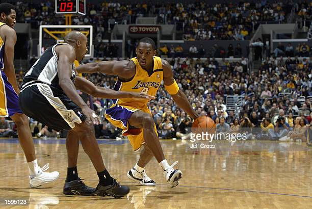 Kobe Bryant of the Los Angeles Lakers drives around Bruce Bowen of the San Antonio Spurs during the NBA season opener at Staples Center on October 29...