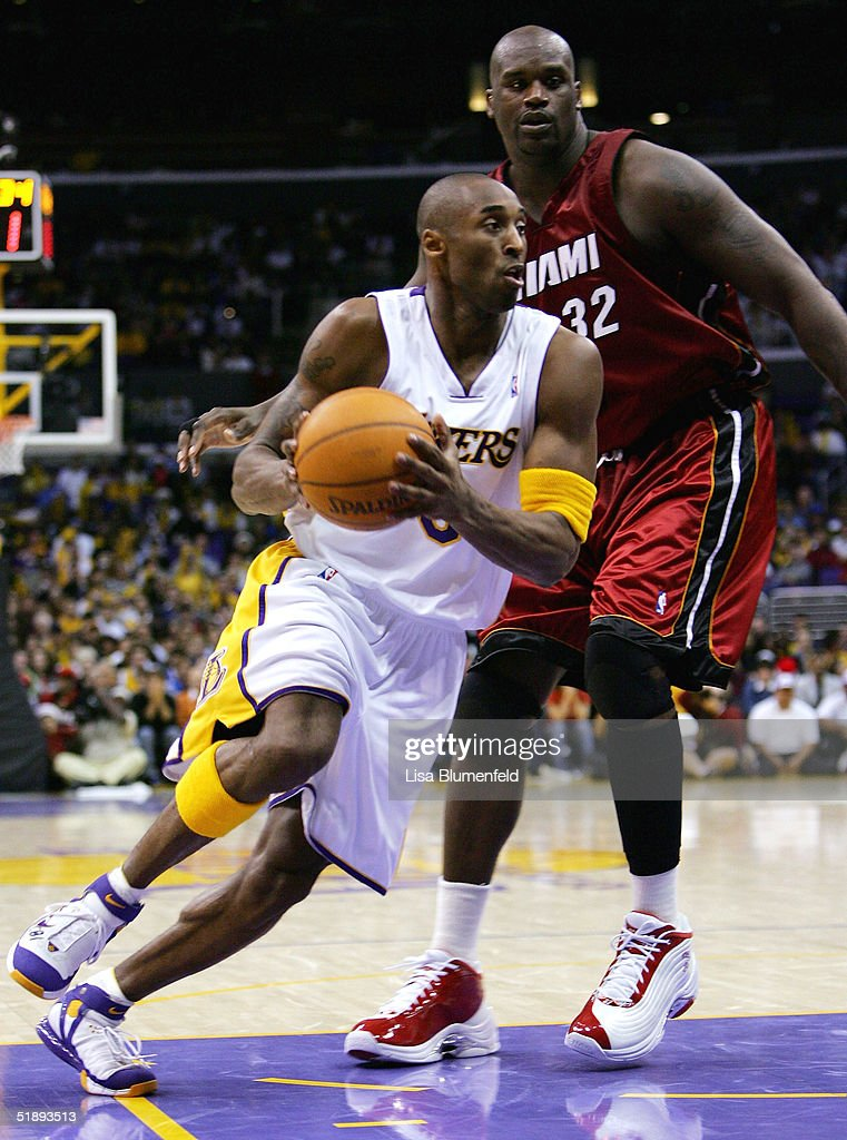 Kobe Bryant of the Los Angeles Lakers drives by Shaquille O'Neal of the Miami Heat on December 25 2004 at Staples Center in Los Angeles California...