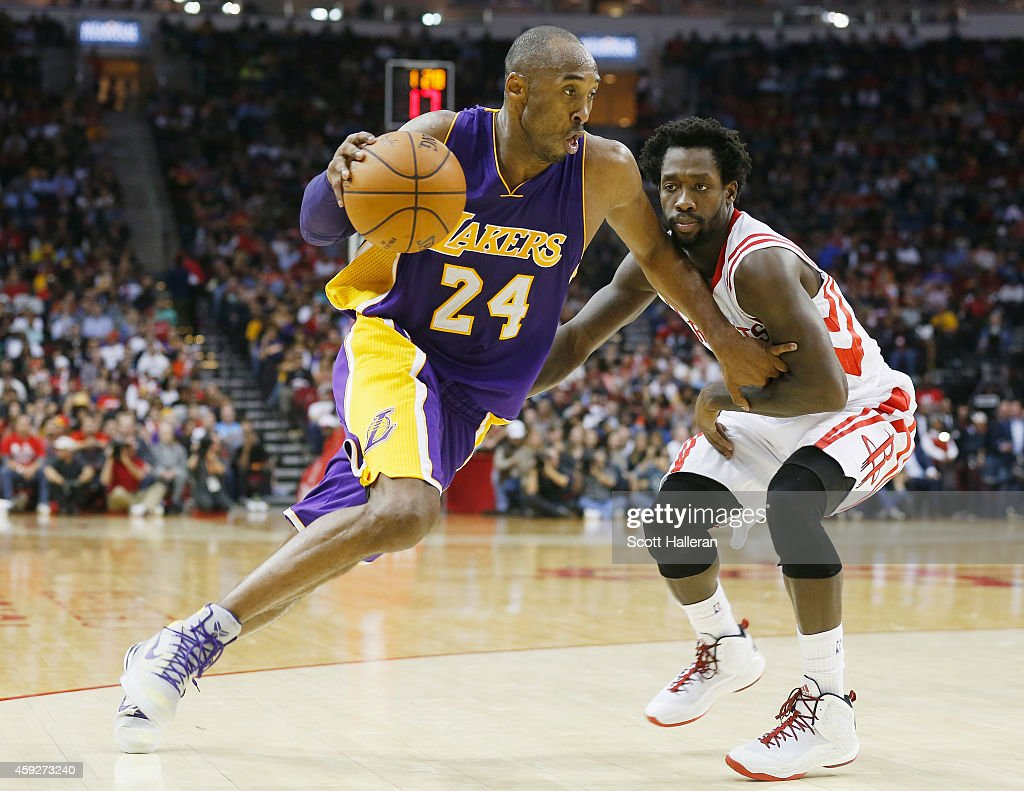 Kobe Bryant #24 of the Los Angeles Lakers drives with the ball against Patrick Beverley #2 of the Houston Rockets during their game at the Toyota Center on November 19, 2014 in Houston, Texas.