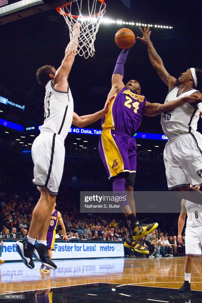 Kobe Bryant #24 of the Los Angeles Lakers dunks against Kris Humphries #43 and Gerald Wallace #45 of the Brooklyn Nets on February 5, 2013 at the Barclays Center in the Brooklyn borough of New York City.