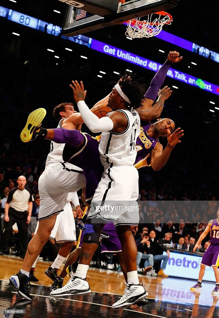 Kobe Bryant #24 of the Los Angeles Lakers dunks between Kris Humphries #43 and Gerald Wallace #45 of the Brooklyn Nets at Barclays Center on February 5, 2013 in the Brooklyn borough of New York City.The Lakers defeated the Nets 92-83.