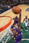 Kobe Bryant of the Los Angeles Lakers goes for a backwards layup against the defense of the Utah Jazz at EnergySolutions Arena on November 26 2010 in...