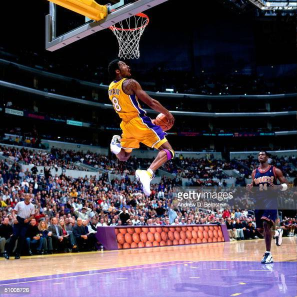 Kobe Bryant of the Los Angeles Lakers goes for a reverse slam dunk as Antonio McDyess of the Denver Nuggets looks on at the Staples Center circa 2000...