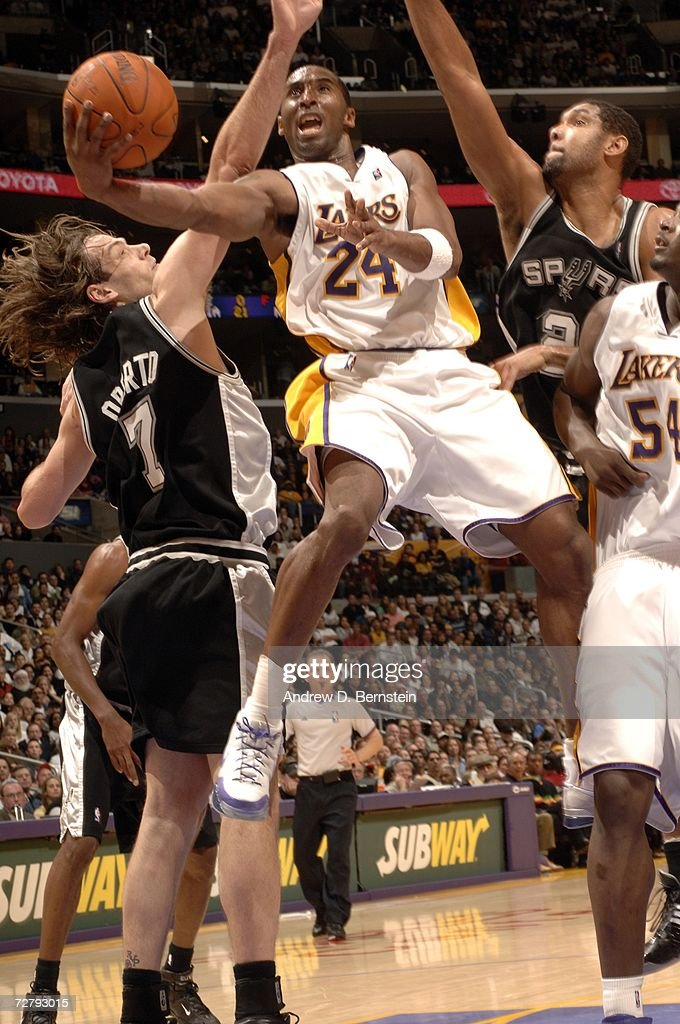 Kobe Bryant #24 of the Los Angeles Lakers goes strong to the hoop against Tim Duncan #21 and Fabricio Oberto #7 of the San Antonio Spurs at Staples Center December 10, 2006 in Los Angeles, California.