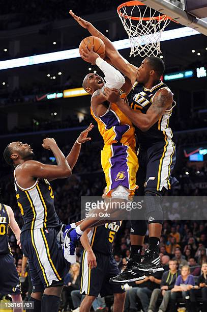 Kobe Bryant of the Los Angeles Lakers goes to the basket against Derrick Favors of the Utah Jazz at Staples Center on December 27 2011 in Los Angeles...