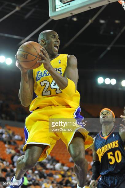 Kobe Bryant of the Los Angeles Lakers goes to the basket against Corey Maggette of the Golden State Warriors during a preseason game at The Forum on...
